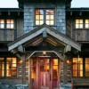 The entry highlights the various reclaimed materials-moss-and-lichen covered logs, shingles, stone-used on the home. While it makes the home feel as if it's old and a long-time part of the site, it announces that what's behind the door is going to be inviting and warm.